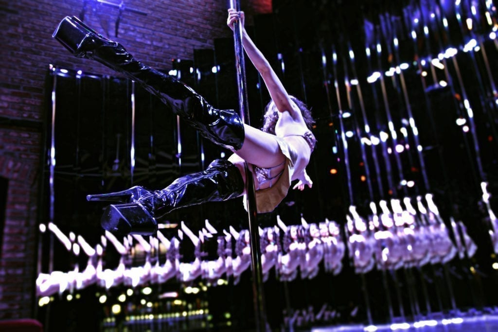 Nina flying around pole from behind
